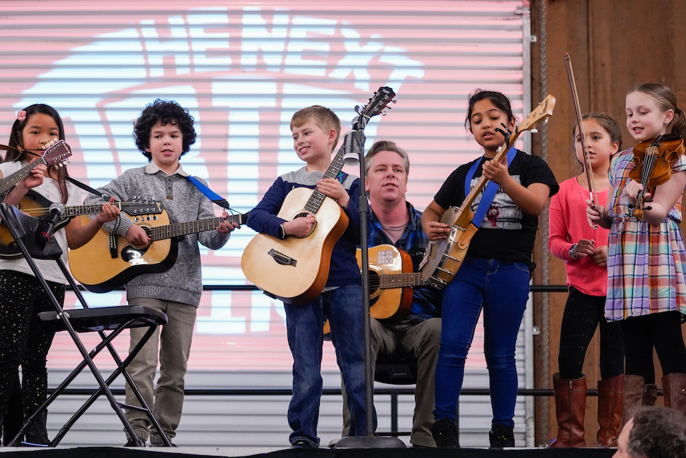 Students singing and playing guitars on stage at The Next Big Think