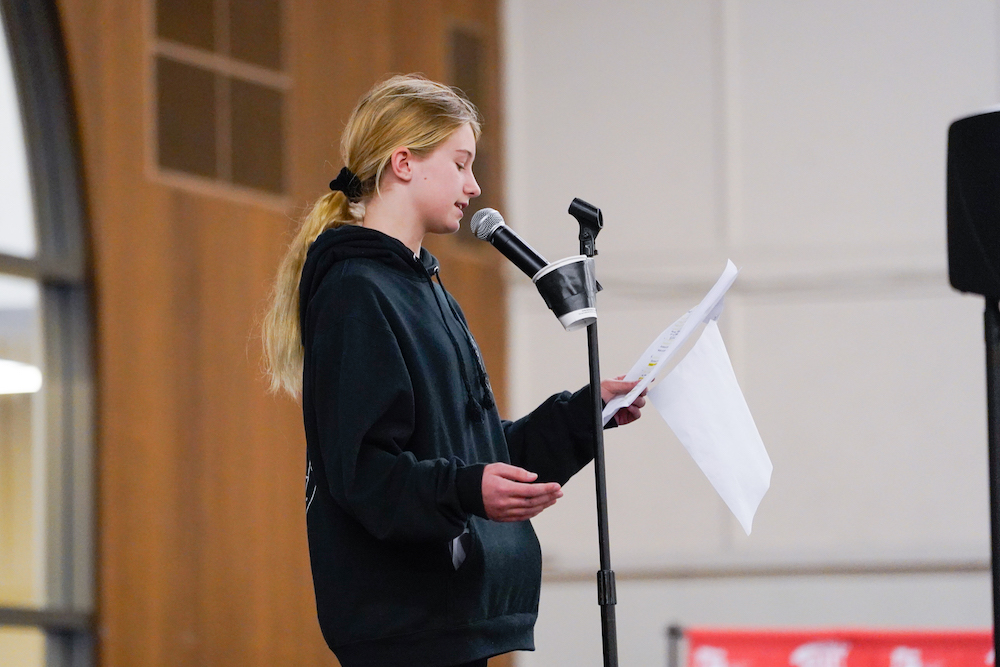 A student reads a poem at The Next Big Think