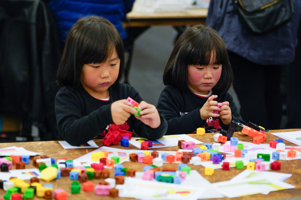 Two young girls play with blocks at The Next Big Think
