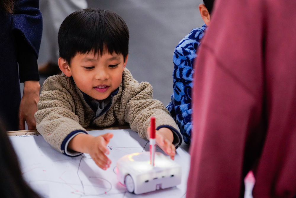 A young student uses a robot to draw on a piece of paper at The Next Big Think