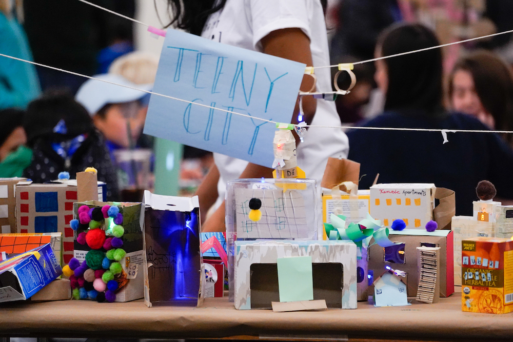 A tiny city made out of paper and other materials on display at The Next Big Think