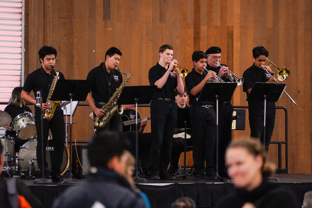 Students play saxophones, trumpets, trombones, and other instruments on stage at The Next Big Think