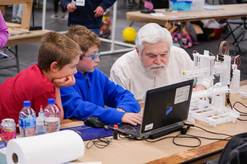 Two young students and an adult use a computer at The Next Big Think