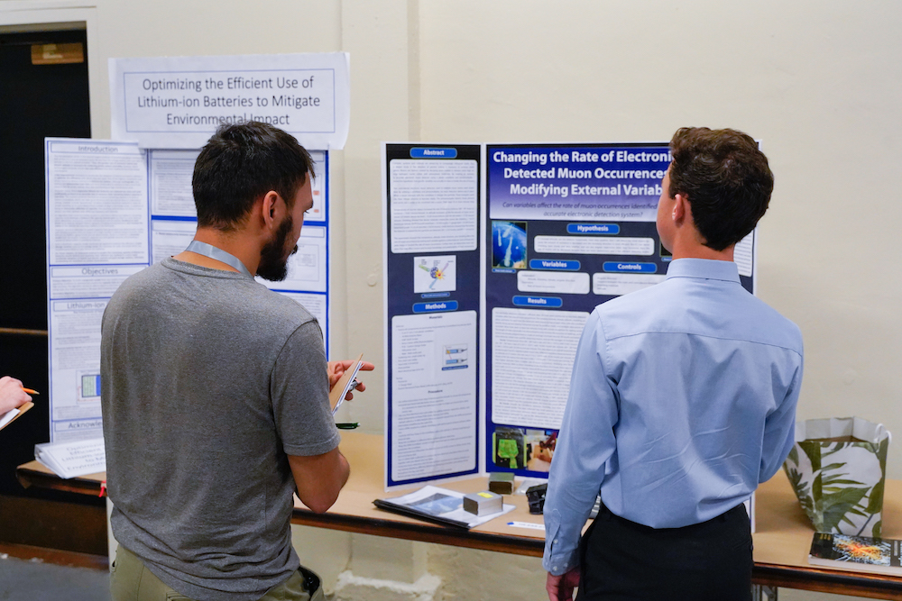 A student shares his STEM Fair project with a judge at The Next Big Think