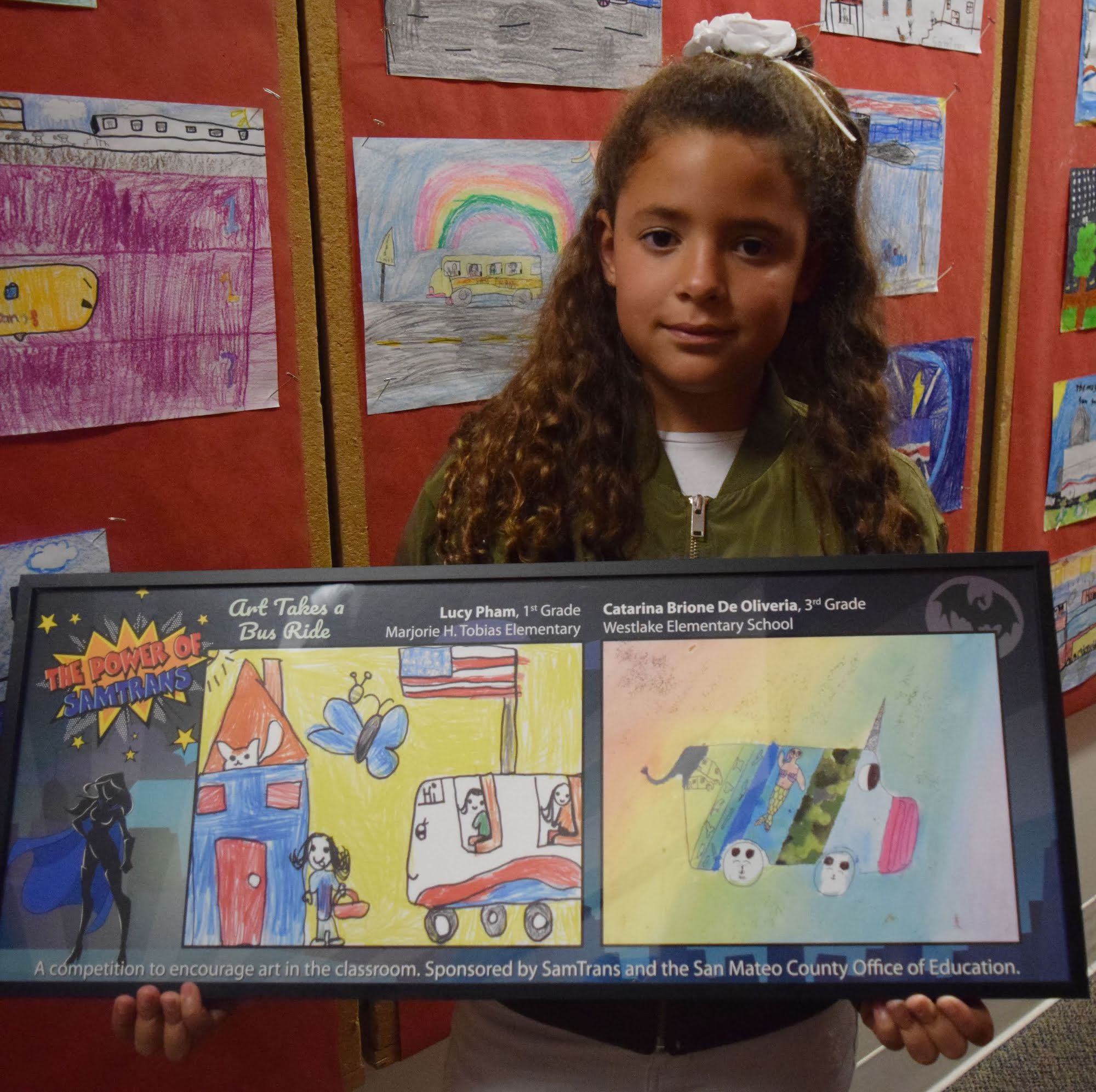 A student shows off her artwork submitted to the Art Takes a Bus Ride competition.