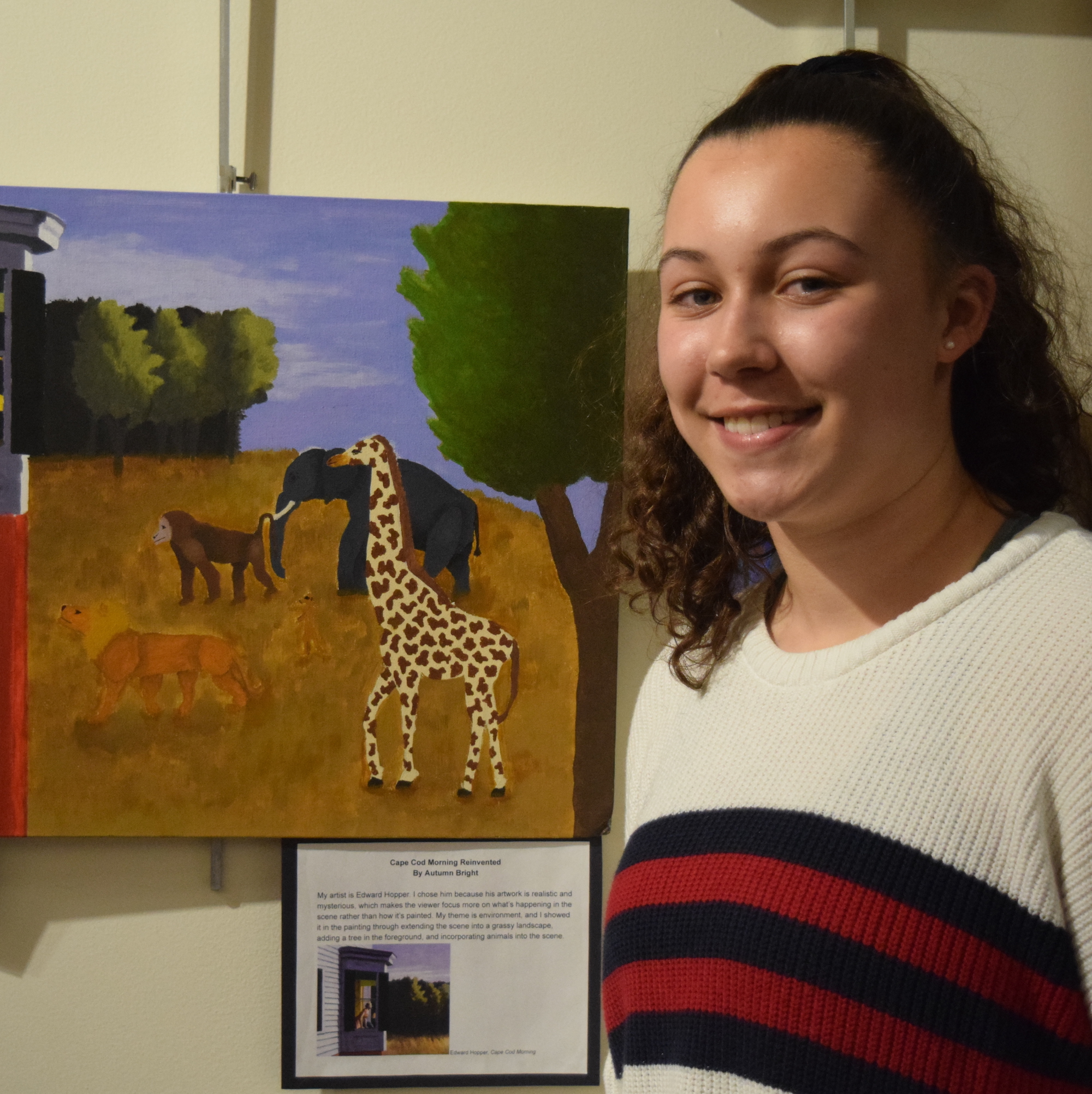 A student stands by her artwork displayed at the San Mateo County Office of Education.
